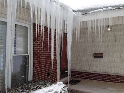 home with long icicles and ice dams roof to deck ice dam removal